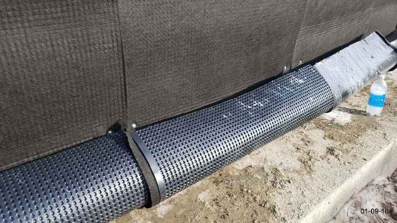 Close up of the panel drain wrap around the 6-inch drain pipe to protect during fill placement.