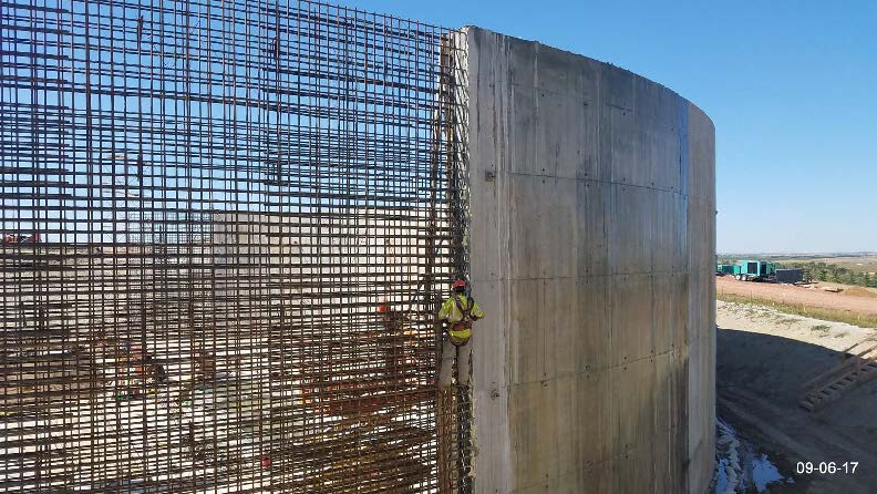 Removal of concrete flash and burnishing the surface of the SE end of wall section #11.