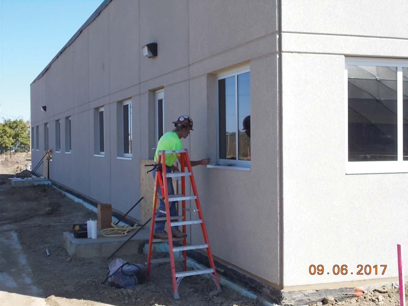 MT Construction sealing the exterior of the windows on the north wall of the administration area.